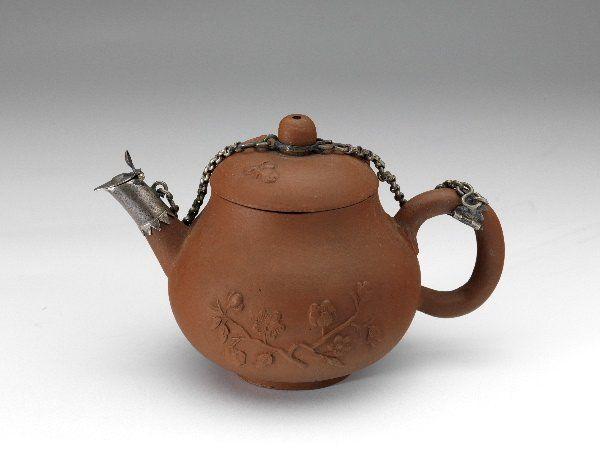 Theepot, rood steengoed, bloemtak in reliëf, zilveren ketting - Milde, Ary de - Museum ArnhemMilde, Ary de (1634 – 1708) Collectie:Toegepaste kunst Materiaal:steengoed, zilver Categorie:Eet-, drink- en keukengerei Afmetingen: hoogte:7.8 cm breedte:12.5 cm diameter:8.0 cm