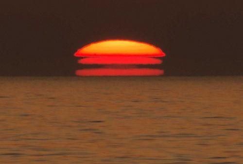 夕日:海に浮かぶハンバーガー 青森・深浦
