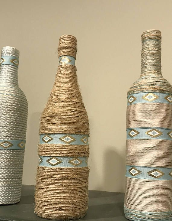 These decorative bottles have a southwestern flair. Made by myself and wrapped by hand, these bottles are not perfect, which definitely adds some charm to them. They are made with jute twine and white and gold yarn with pastel decorated ribbon. Thank you for shopping with me and I hope