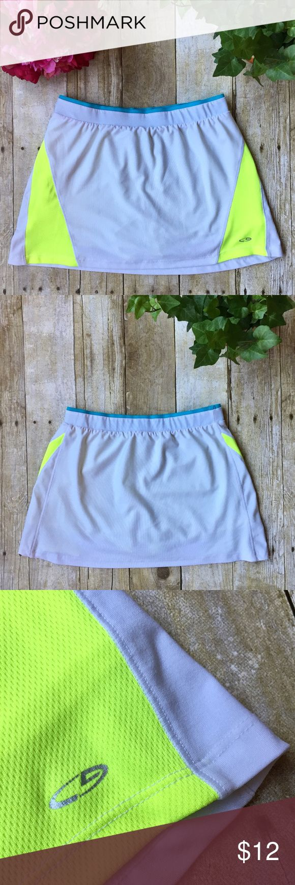 Champion Active Skirt/Skort Girls L Women's XXS Champion Active Skirt/Skort Girls L Women's XXS  • Size Girls Large • Can fit Women's size XXS • Active | Athletic | Tennis | Cheer | Dance | Skirt/Skort • White w/ electric yellow side panels & turquoise trim • Built-in electric/neon yellow shorts • Breathable, sweat-wicking, dri-fit-like material • Polyester/Spandex • Excellent used condition; no flaws   Make an offer! Sorry, no trades! 💛 Champion Bottoms Skorts