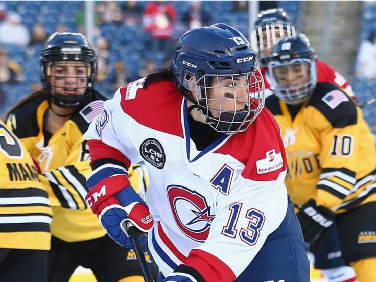 Caroline Ouellette #13 of the Les Canadiennes (CWHL) carries the puck against the Boston Pride (NWHL) during the Outdoor Womens Classic at Gillette Stadium on December 31, 2015 in Foxboro, Massachusetts.