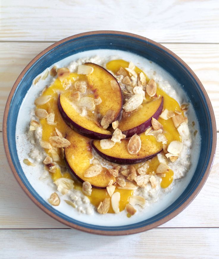Coconut Porridge with Mango Puree - porridge made with coconut milk, topped with summary fruits, toasted almonds cinnamon and a sprinkling of brown sugar.