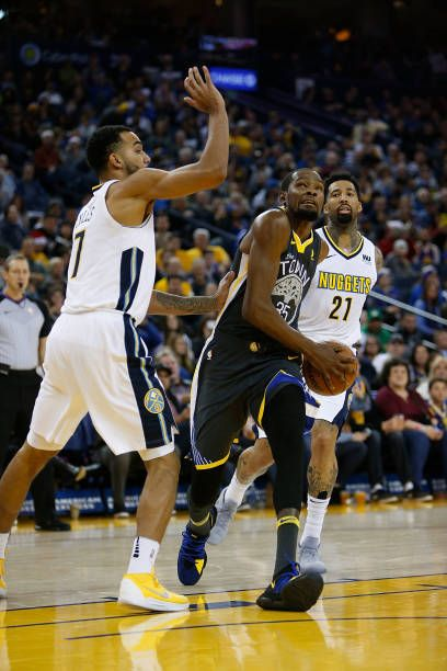 Kevin Durant of the Golden State Warriors drives to the basket against Trey Lyles of the Denver Nuggets at ORACLE Arena on December 23 2017 in...