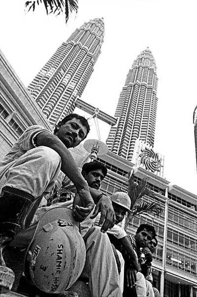 Bangladeshi migrant workers works in front of the Petronas Tower. Kuala Lumpur. Malaysia. Shahidul Alam/Drik/Majority World