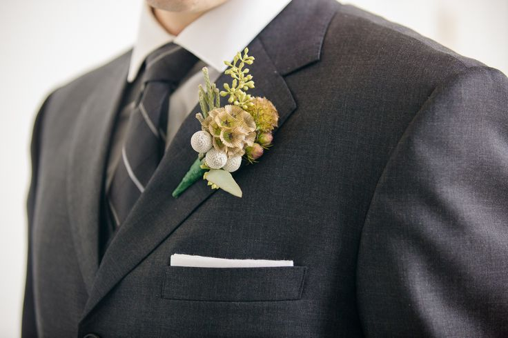 A rustic boutonniere, made up of Seeded Eucalyptus, Scabiosa Pods, silver Brunia Balls, and Protea, made by Ethereal Array Creations and Events at Marigny Opera House