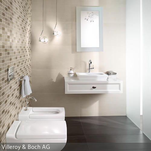 Durch die großen Fliesen an der Wand und dem Boden entsteht eine einheitliche und geordnete Optik. Die beigefarbenen Mosaikfließen lockern diese visuell auf,  …