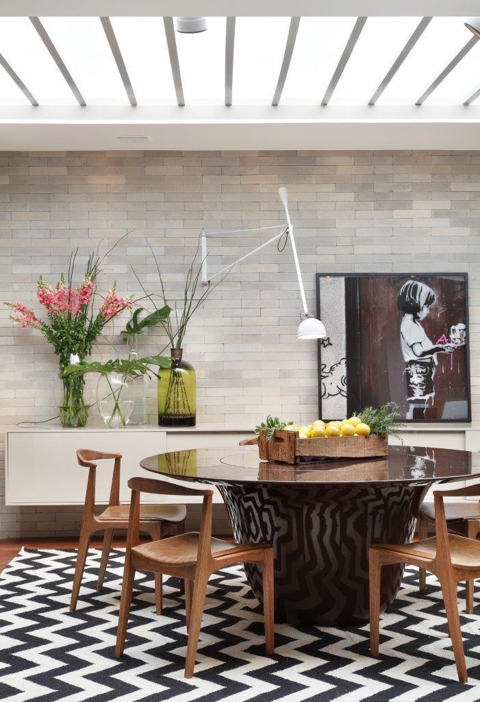 Mesa de jantar Sino com acabamento em laca preta, aparador suspenso Simple com portas de correr em laca, cadeiras Diva assinada pelo Studiobola.