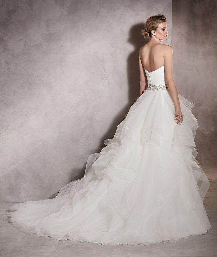 Платье ALBANIA силуэта «принцесса», с вырезом в форме сердца, поможет невесте ощутить себя подлинной героиней своего знаменательного дня. Характерный элемент этого свадебного платья из тюля и нейлона — каскад волнистых оборок. Это пышное платье полно движения.