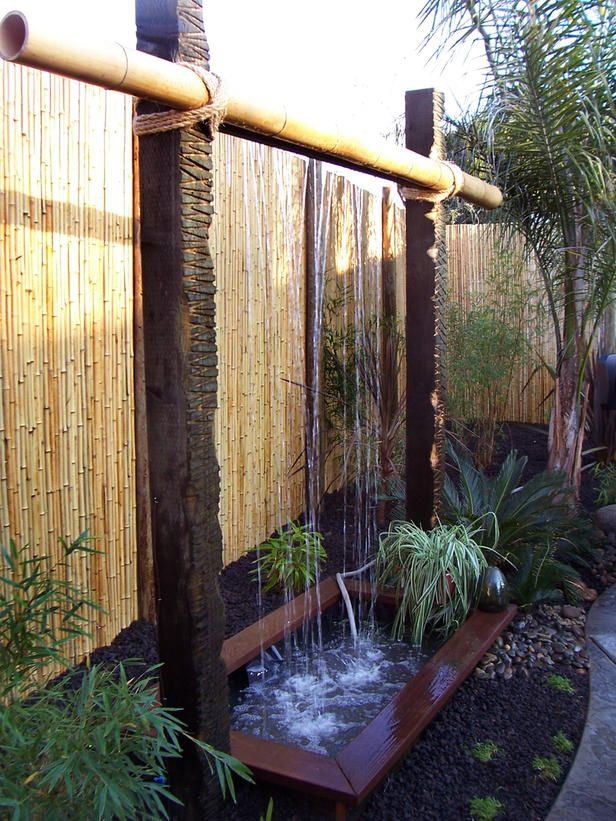 Exotic Escape  The bamboo fence complements the distressed wood rods of this exotic water feature and creates a dimensional backdrop for the waterfall. A large bamboo piece is attached to the rods with twine for a natural look that makes you feel as if you're at a tropical waterfall.