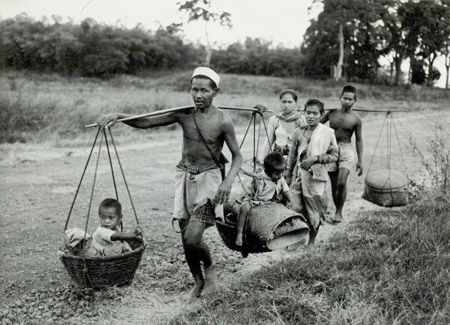 Indisch gezin op de vlucht op de weg tussen Soemedang en Bandoeng, kinderen worden vervoerd in manden aan een bamboe stok, eerste politionele actie Midden-Java Indonesië, tussen 23 en 27 juli 1947.