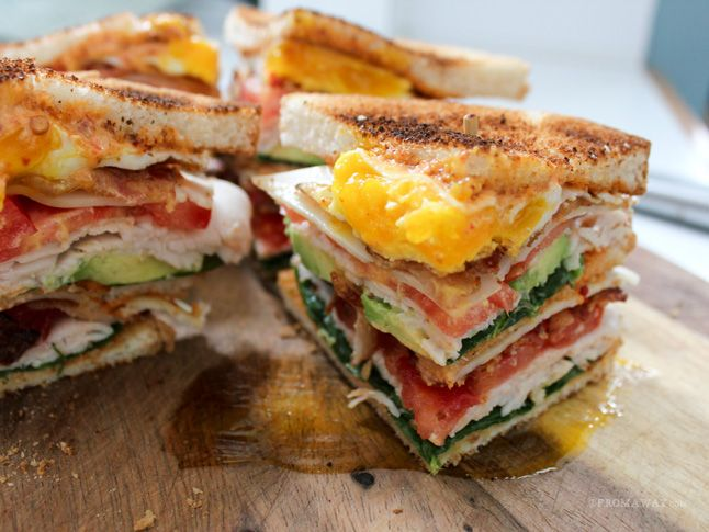 """Today's sandwich is the """"California Club with Chipotle Mayo."""" It combines turkey, Swiss cheese, bacon, spinach, tomato, avocado, a fried egg, and chipotle mayonnaise on three slices of toasted white bread."""