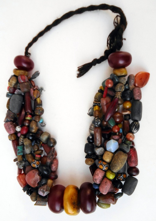 Africa | Berber necklace with 7 big resin amber beads and 7 strings with lots of beads; trade beads, ceramic beads, and I counted even 5 worn out plastic beads, the most recent addings. The majority is 100 years and older, some big carnelians must be even 300 years old. Most beads are, but not every bead is, in perfect condition. | 600 Euro