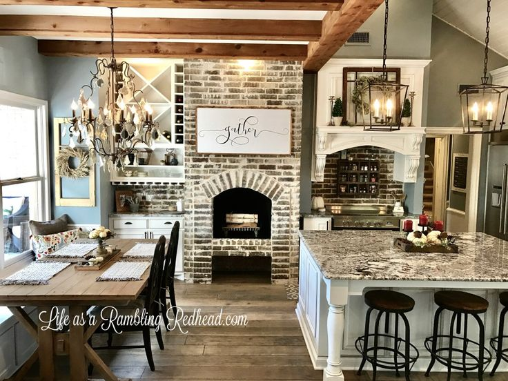 love the table with bench seat at the window, love the wood beams above, the hanging square lights and island, colors, brick.