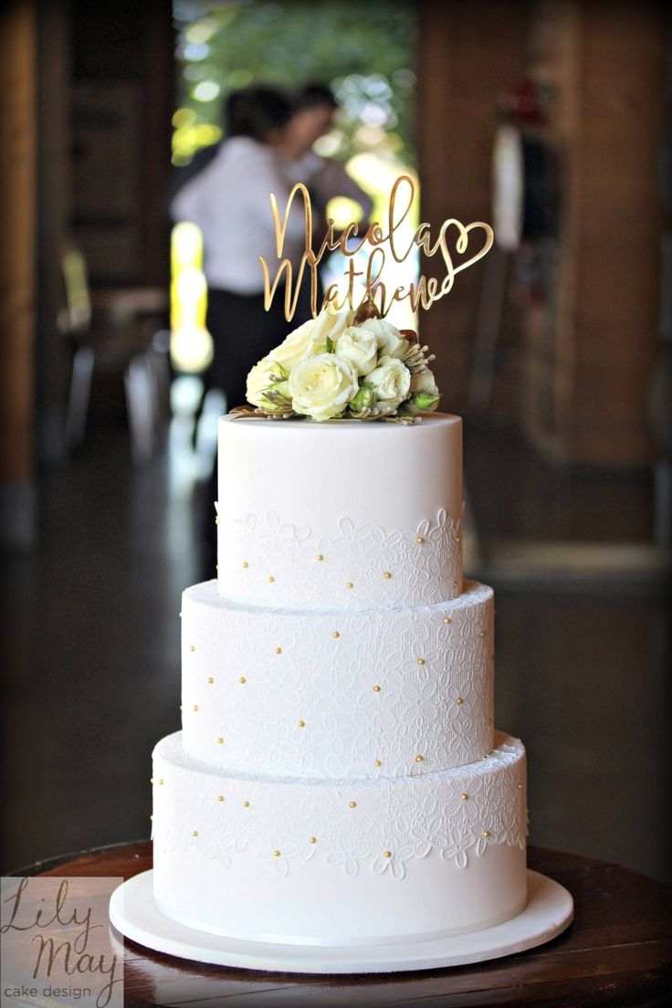 Simply elegant crisp white wedding cake finished with edible lace, gold cachous, fresh florals & a personalised cake topper.