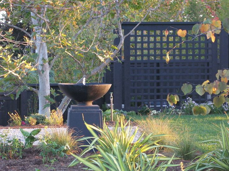 If your garden walls cannot be changed, consider building one or more screens and painting them black to achieve the same look. Screens also cover a multitude of design sins, such as trash cans and HVAC units.