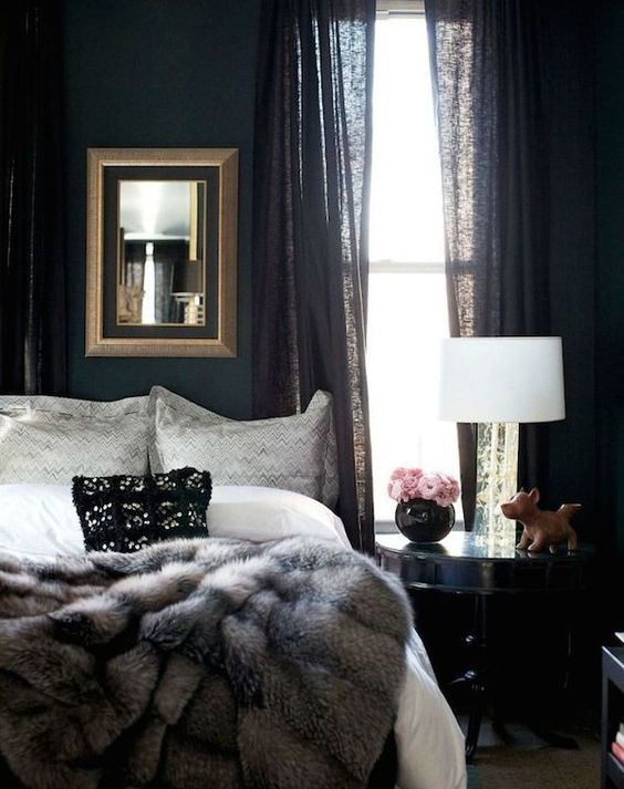 moody bedroom with black curtains, a fur blanket and a framed mirror