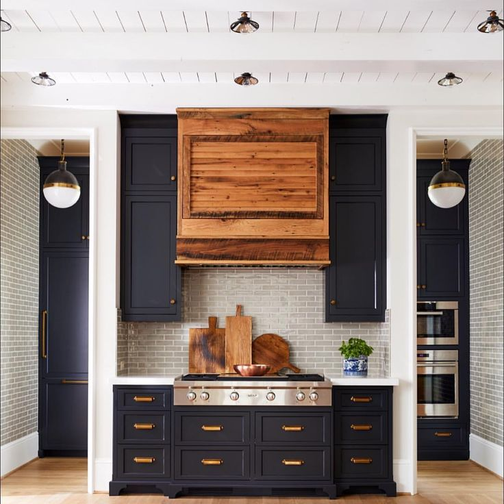 One of our latest #NewOldCustomHome favs! The perfect color of blue black cabinets paired with a reclaimed oak hood, antique brass pulls,…