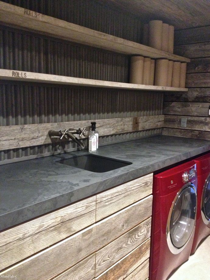 rough rustic industrial laundry room with wood cabinets and corrugated metal backsplash via Slim Paley