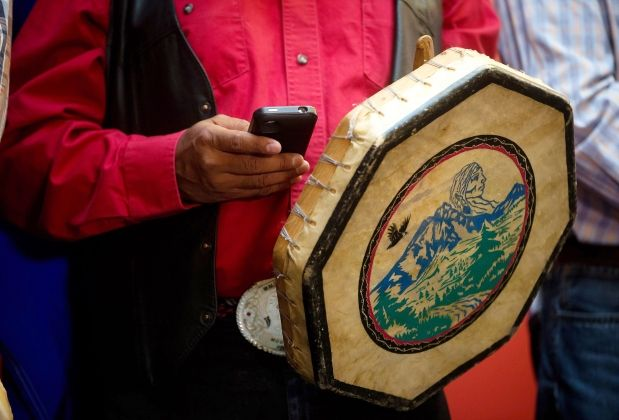 Chief Roger William, of the Xeni Gwet'in First Nation, checks his iPhone while holding a traditional drum during a news conference in Vancouver, after the Supreme Court of Canada ruled in favour of the Tsilhqot'in First Nation, granting it land title to 438,000-hectares of land on Thursday June 26, 2014.