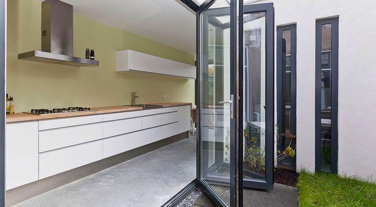 Foto van aanbouw met zicht op keuken en vouwdeuren. Bob
