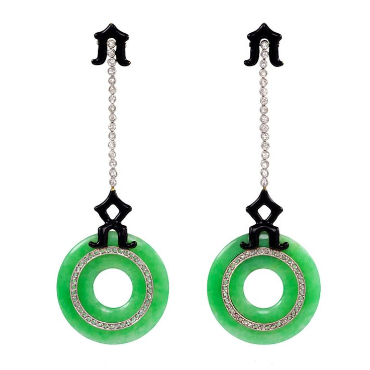 Art Deco Black Enamel Jade Diamond Earrings. A pair of Art Deco pendant earrings comprised of a line of collet set diamonds terminating in jade disc pendants inlaid with diamond circles and embellished with black enamel ornaments in the form of stylized pagodas, in 18k gold and platinum. France.