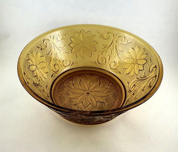 Indiana Glass Amber colored Fruit bowl.  Large Fruit bowl or Serving bowl is 8 1.4 inches wide and 3 1/2 deep.  Floral design all around the bowl.  Has a chip in the rim.  Thick glass material.  1925-1985