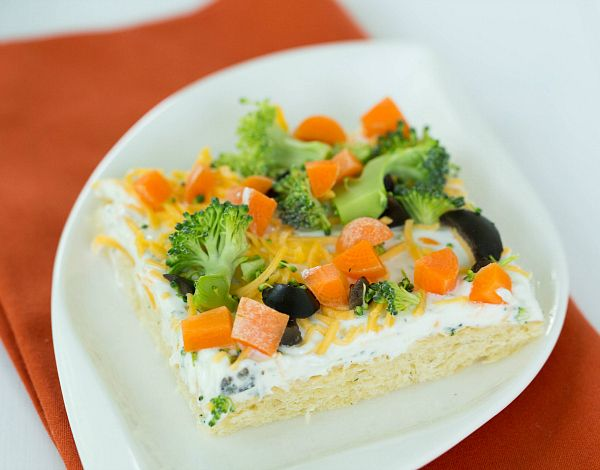 VEGGIE PIZZA APPETIZER  2 packages (tubes) refrigerated crescent rolls  16 ounces sour cream  1 (1-ounce) package Hidden Valley Ranch seasoning packet  ½ cup shredded cheddar cheese  ½ cup chopped carrots  ½ cup chopped broccoli  ¼ cup chopped black olives