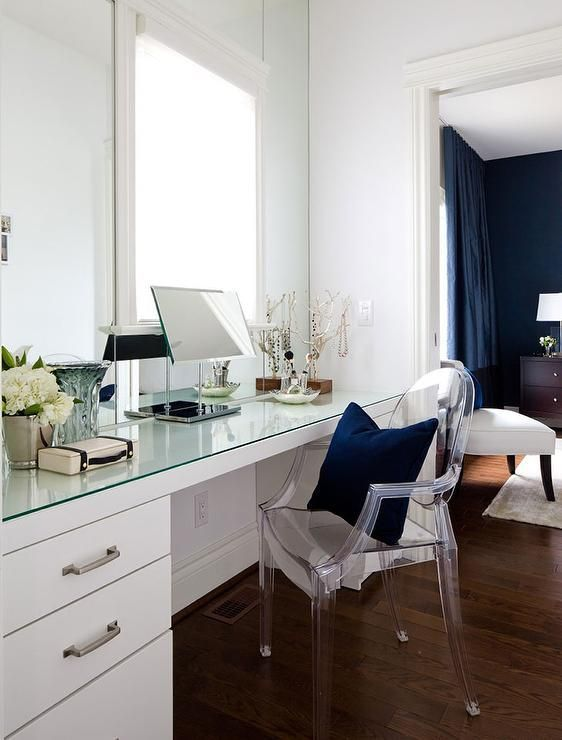 Chic dressing room features a full length glass top dressing table paired with a Kartell Ghost Chair placed under a window. #VanityChair