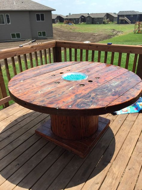 DIY Rustic Wooden Spool Gas Fire Pit Table (fire glass) that Glows in the Dark!  Follow the steps we took to repurposed this wooden spool and make it so unique. For directions:  http://www.revivesalonsf.com/blog/diy-rustic-wooden-spool-fire-pit-table/