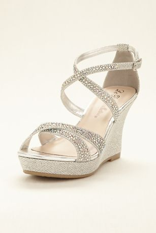 """Dance the night away in these fabulous crystal encrusted cross strap wedge sandals by Blossom! Cross strap wedge sandals adorned with sparkling crystals on straps. Ankle strap provides added support. Heel height: 3.5"""". Fully lined. Imported."""