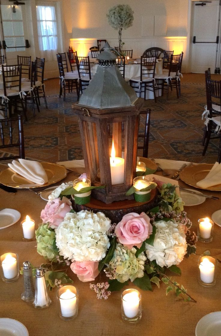 A lantern with log bottom and pink roses hydrangea