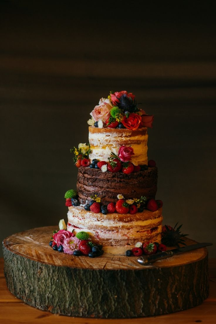 A three layered naked cake. Two tiers of victoria sponge and two tiers of chocolate. Lucy and Kevin's Hitchin Lavender Farm wedding, featuring a Kata Tipi, jewel tones, rustic styling and glorious golden hour light. Creative UK and destination wedding photography by www.babbphoto.com