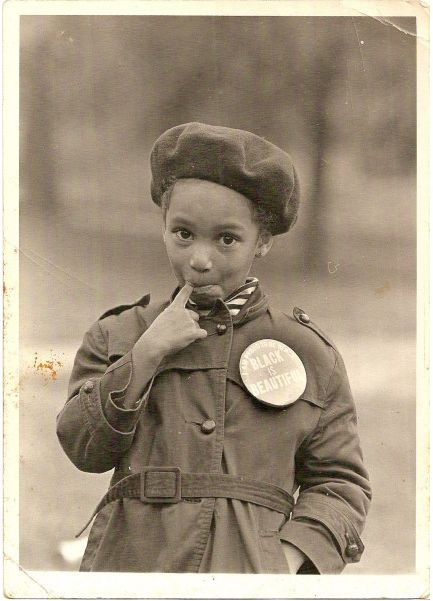 "Unidentified African American girl. Coat button reads, ""Black Is Beautiful."""