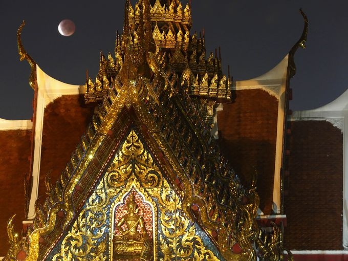 A lunar eclipse is visible behind the Plubplachai temple