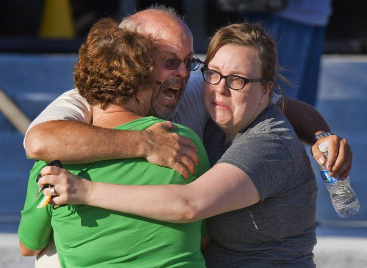 Tom Sullivan, center, embraces family members outside Gateway High School where he had been searching franticly for his son, Alex Sullivan, who had gone to see the Batman premiere for his 27th birthday.