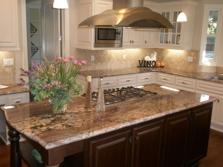 autumn rose crema bordeaux granite counters with dark wood island and white perimeter cabinets