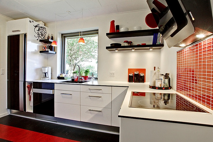 I et rigtig hyggeligt og velindrettet hus i Kolding findes dette flotte køkken i moderne stil i farverne hvid, sort og rød. Klik for fotos af boligen.    A simplistic modern kitchen with a little bit of edge kept in the colors of red, white and black. The kitchen belongs to a nice and welcoming house in Kolding, Denmark.  Keywords: kitchen, black, white and red, modern.