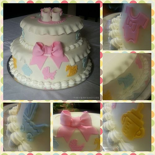 Baby Welcoming Cake - Mud chocolate cake covered with white fondant as well as a skirt on the top. It is decorated with baby themed silhouettes, flowers, a pink bow on the back and white and pink booties on the top. The name is made with royal icing and piped in a certain way to add texture.