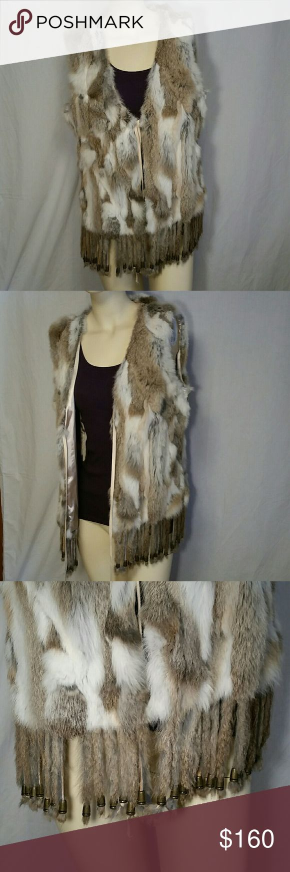 """Alberto Makali Genuine Rabbit Fur Vest w/ Fringe Beautiful 100% genuine rabbit fur vest from Alberto Makali! The fringe on the hem gives this piece a very bohemian festival feeling. There are leather straps so you can tie it closed or just leave it hanging open. Size Medium Measurements laying flat with the two chest hems touching, not overlapping: Chest 18"""" Length 24"""" ...plus about another 4"""" of the fringe There is some wear  to the fur under one of the armpits and one of the fringe pieces…"""