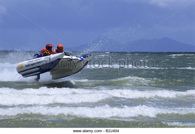 Competitors in annual Cape Agulhus inflatable boat race airborne over small waves South Africa sport adventure - Stock Image