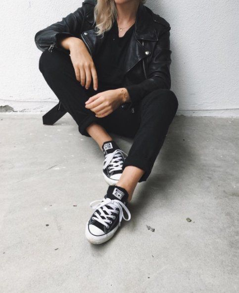 All black everything in a leather jacket, a tee, slim cuffed jeans, and sneakers.