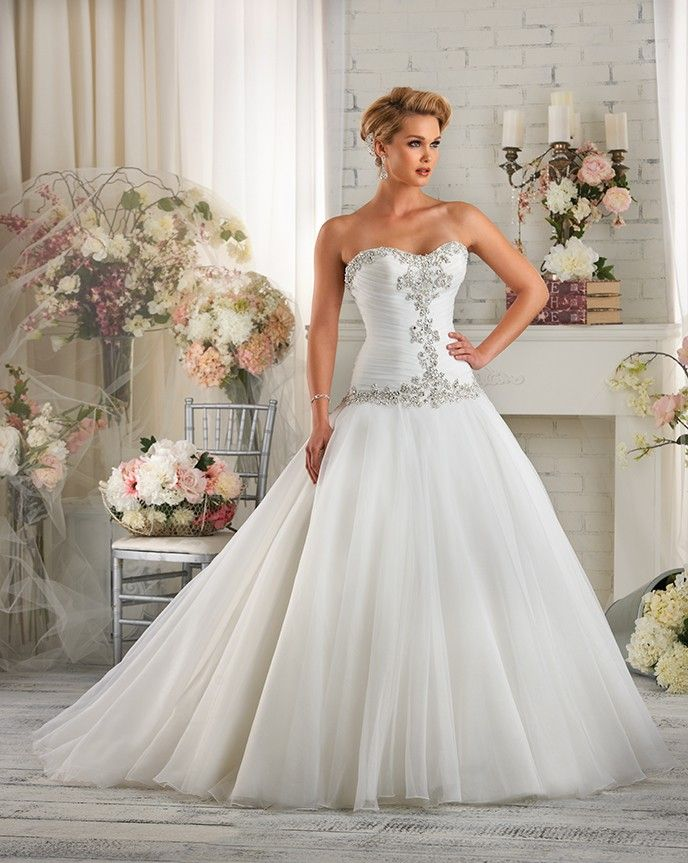 421 Bonny by Bonny Bridal - A modern look with a traditional silhouette. Ornate beading frames the bodice and sweetheart neckline. The bodice is slimming with delicate pleating details and a corset back. The soft full circle cut skirt extends into the semi-cathedral train.