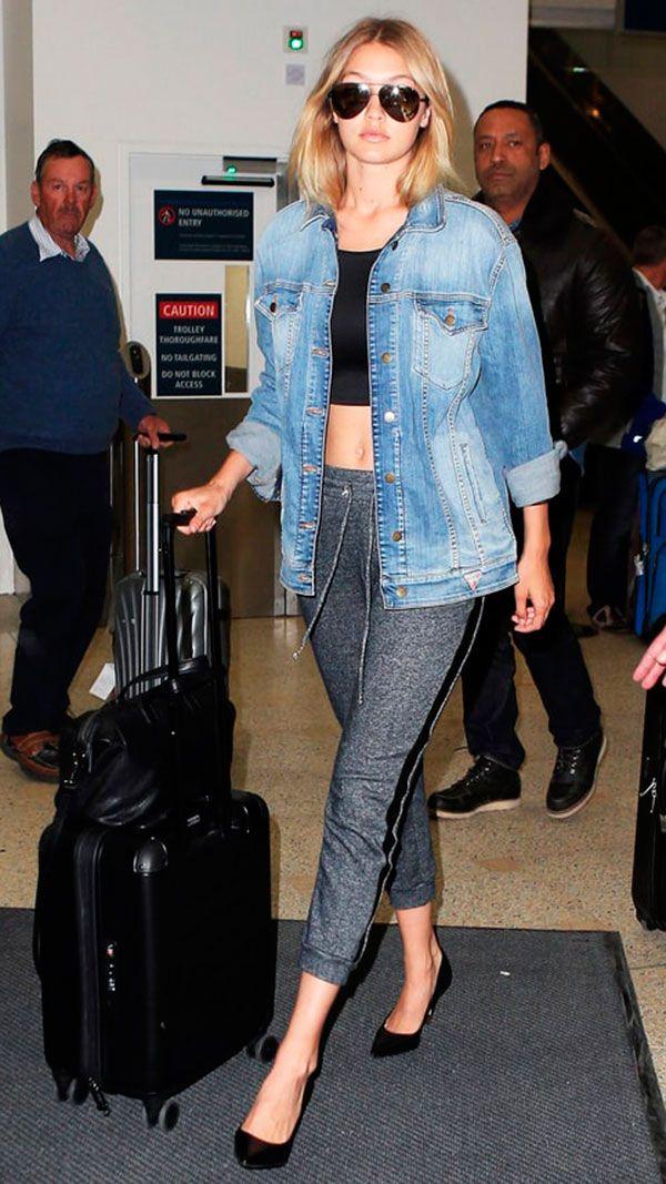 Street style look Gigi Hadid cropped preto, calça jogging cinza, salto scarpin e jaqueta jeans.