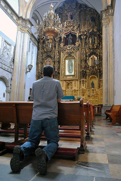 Kneeling to pray. The tallest man is the one on his knees.