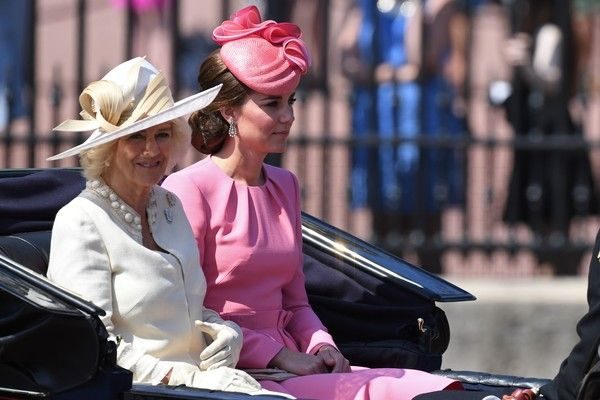 Kate Middleton Photos Photos - Britain's Camilla, Duchess of Cornwall (L), Britain's Catherine, Duchess of Cambridge travel in a horse-drawn carriage past Buckingham Palace on their way to Horse Guards Parade for the Queen's Birthday Parade, 'Trooping the Colour', in London on June 17, 2017....The ceremony of Trooping the Colour is believed to have first been performed during the reign of King Charles II. In 1748, it was decided that the parade would be used to mark the official birthday of…