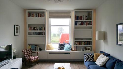 een idee voor om het raam in de woonkamer. Om de radiator een bank/kast en aan de linkerkant een hoge kast en de rechter een stuk eruit voor de tv.
