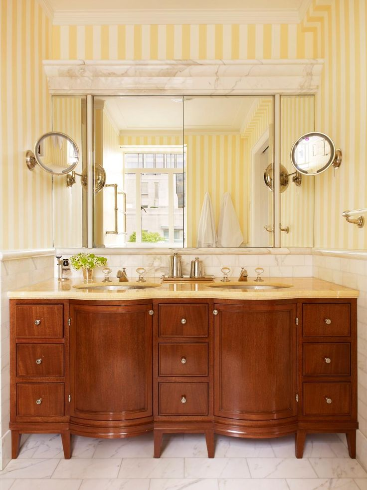 This yellow striped wallpaper and an elegant hardwood vanity speak to the overall traditional style found in this posh New York City apartment.