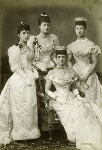 The Royal Collection: Alexandra, Princess of Wales, with her daughters, 1893-Photograph of the Princess of Wales, later Queen Alexandra and her three daughters. From left to right: Princes Maud, standing; Princess Victoria, standing behind her mother's chair; the Princess of Wales, seated, fan on her lap, wearing ornate necklace, tiara; Princess Louise, Duchess of Fife, standing. They are dressed in evening gowns