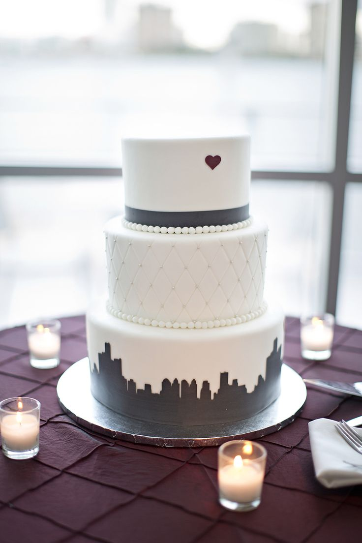 Detroit skyline silhouette at the bottom of this gorgeous wedding cake | Waterview Loft at Port Detroit | Photo: Van De Steene Photography