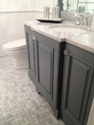 Stunning guest bath with gray bathroom vanity paired with carrara marble countertop and subway tile backsplash. Gray bathroom cabinets with crystal knobs and polished nickel faucet kit. Bathroom floor composed of marble basketweave tiles and subway tile baseboard.. by Mudgey